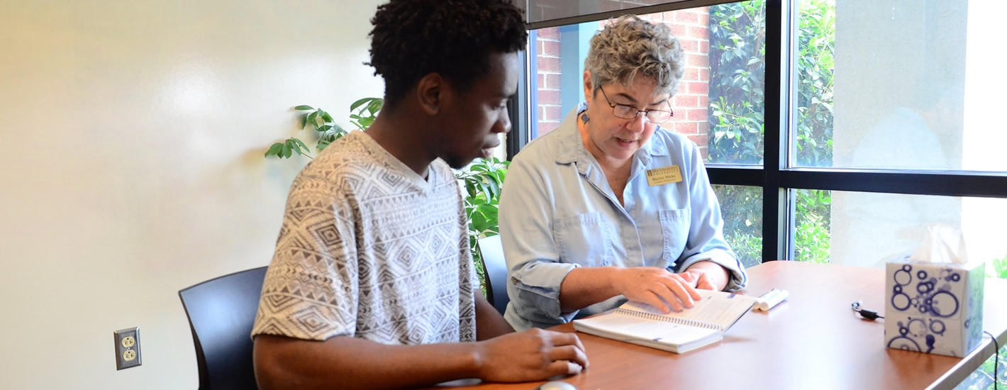 Writing Consultant Baylor Hicks work with a student