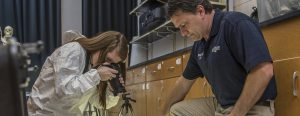 Professor Dave Pauly assists a student with forensic photography.