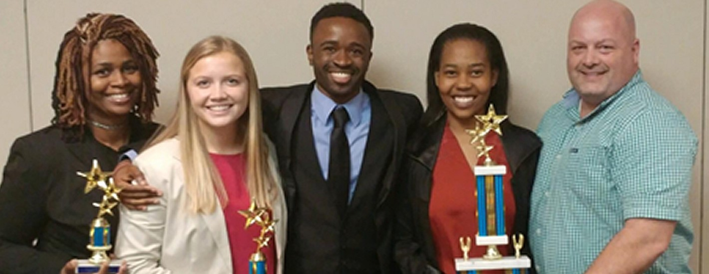 Team members, Teressa Boone, Ally Nagel, Fernando Chivela, and Nomfanelo Hlophe, hold up their trophies with assistant coach, Dr. John Edwards.