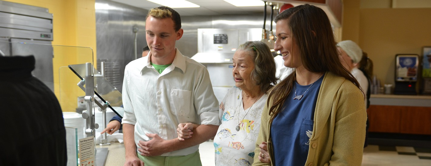 Students assist elderly guests for an annual Thanksgiving celebration