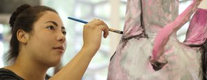 A student paints a 3-D sculpture