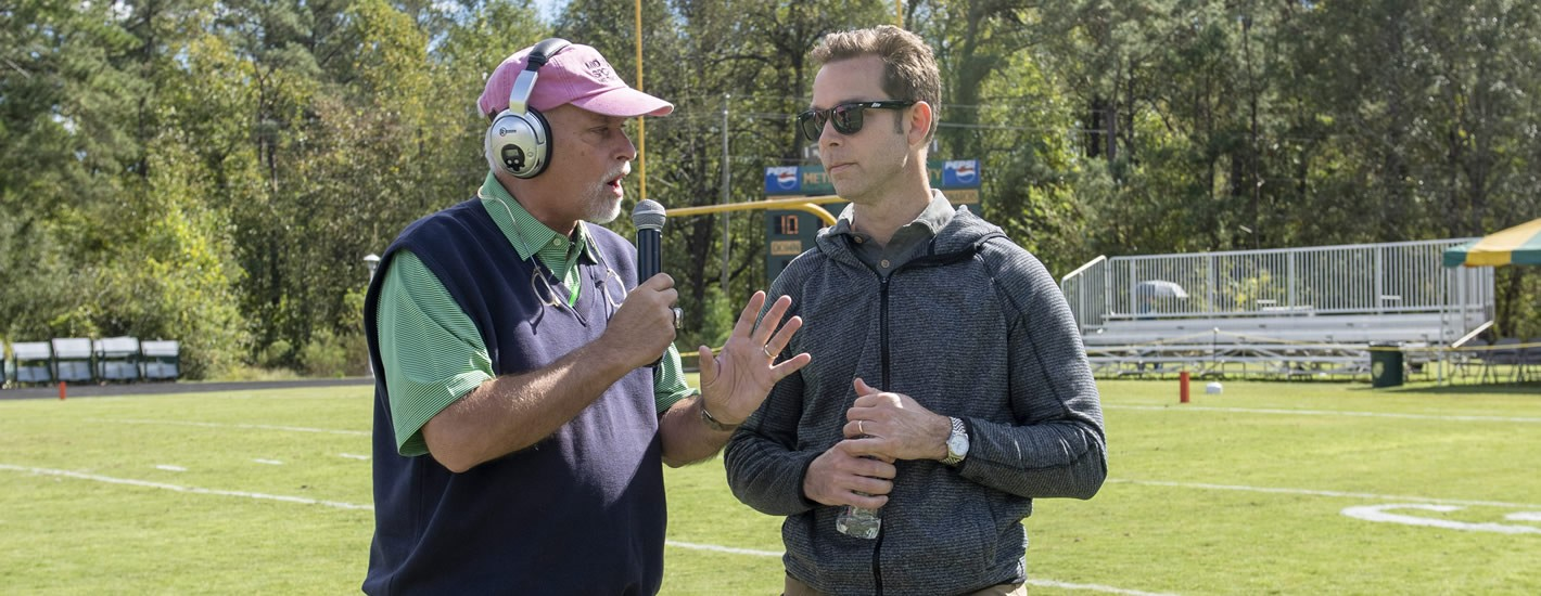Alumnus Steve Driggers conducts an interview on the football field