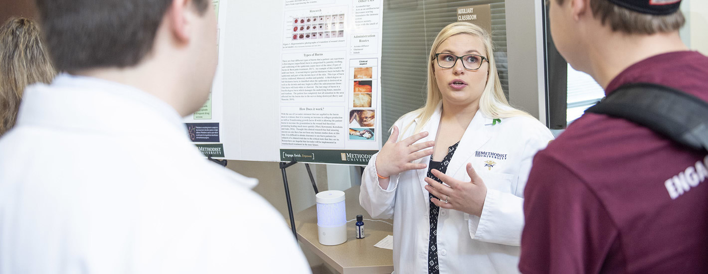 A student nurse presents her research poster