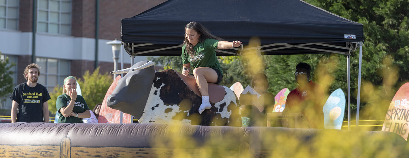A student rides the mechanical bull at Spring Fling