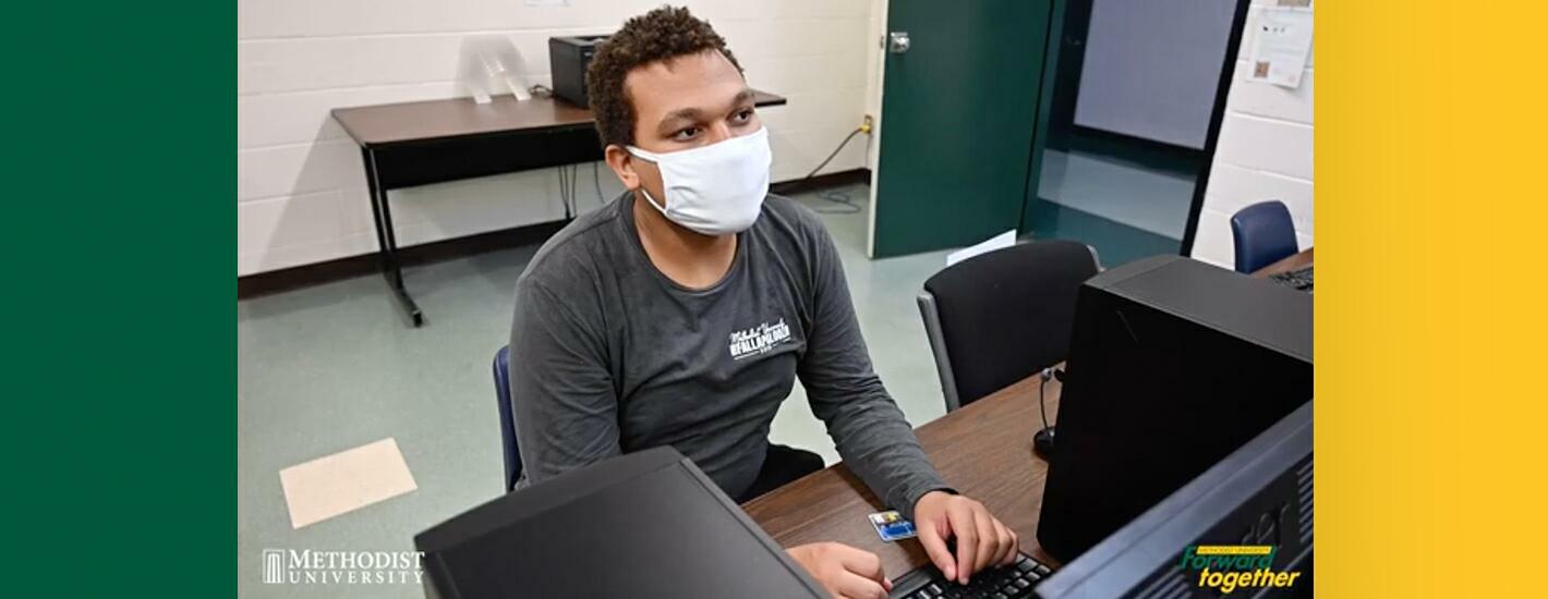 A masked student uses the Computer lab