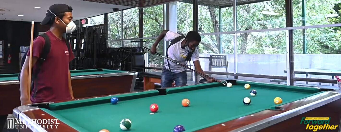 Masked students playing pool
